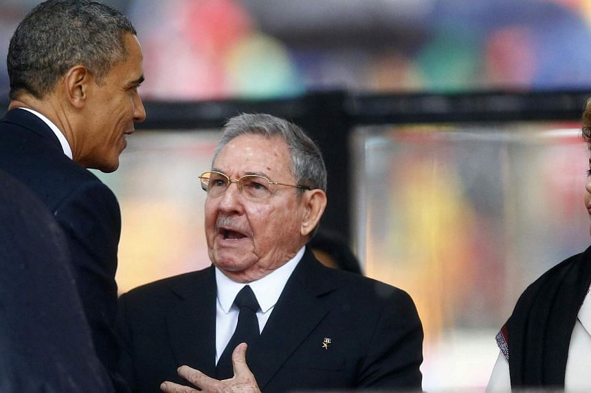 US President Barack Obama (left) greets Cuban President Raul Castro (centre) before giving his speech, as Brazil's President Dilma Rousseff looks on, at the memorial service for late South African President Nelson Mandela at the First National Bank s