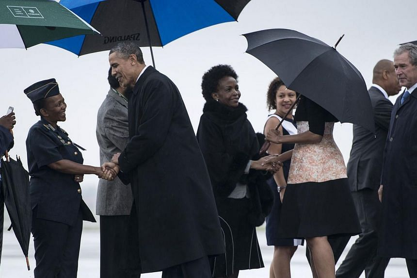 US President Barack Obama (centre) is greeted while arriving with US first lady Michelle Obama (second right), former US President George W. Bush (right) and others at Waterkloof Air Base on Dec 10, 2013 in Centurion, South Africa. Mr Obama arrived i