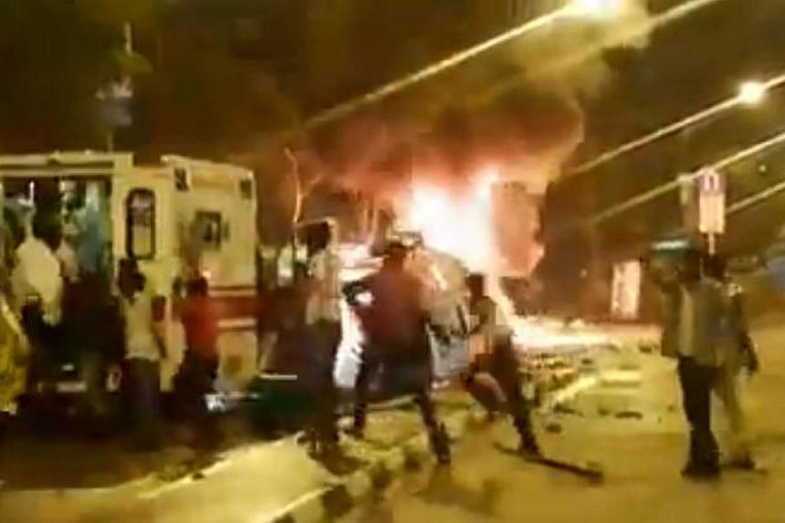 A video posted on Facebook on Tuesday shows rioters pelting police and paramedics with objects as they fled from an ambulance where they were taking cover. Some workers nearer the ambulance, however, were helping the officers out. -- PHOTO: SCREEN CA