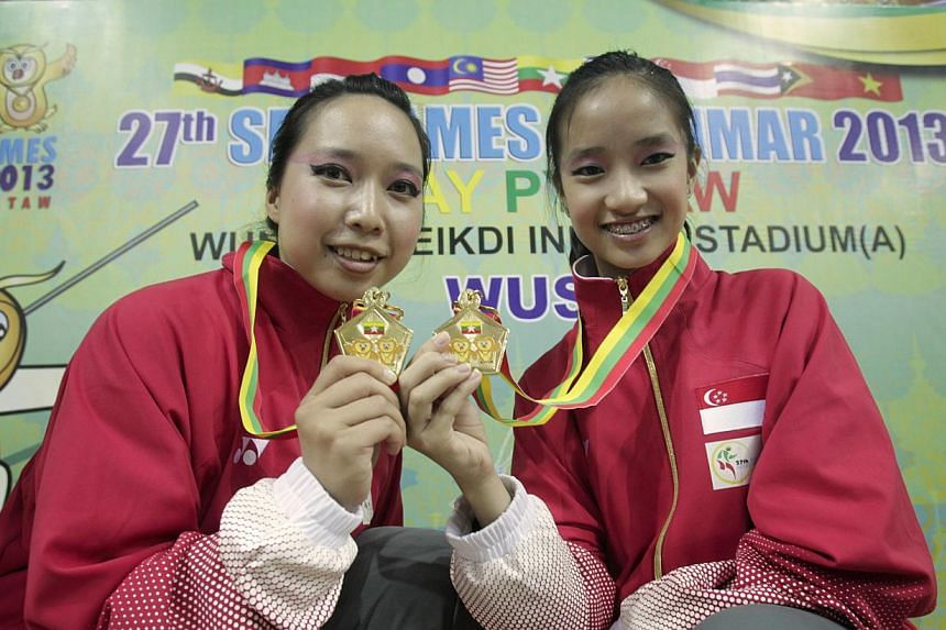 Singapore's Valerie Wee (left) and Vera Tan (right) with their gold medal from women's duilian (barehand) event for wushu in the 27th SEA Games in Wunna Theikdi Indoor Stadium, Naypyidaw, Myanmar, on 10 Dec 2013. -- ST PHOTO: KEVIN LIM