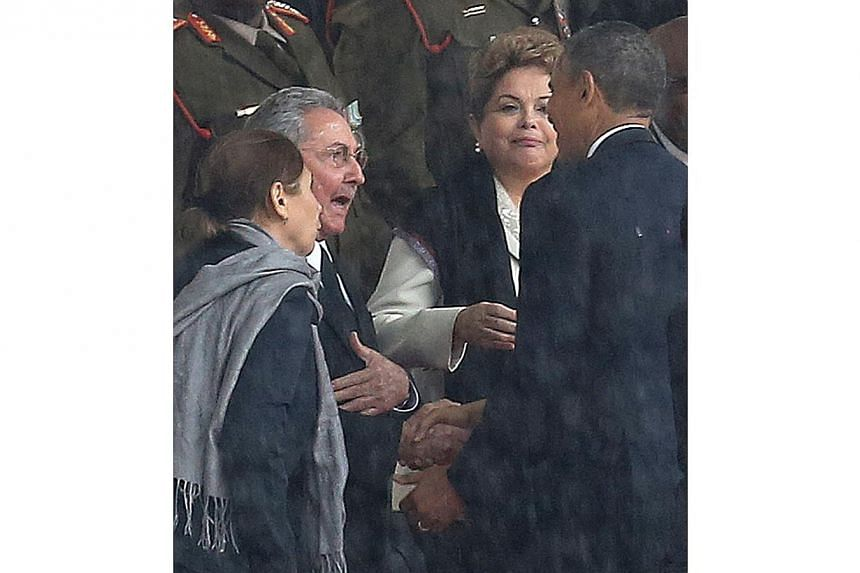 United States President Barack Obama shakes hands with Cuban President Raul Castro as Brazilian President Dilma Rouseff looks on at centre at the FNB Stadium in Soweto, South Africa, in the rain for a memorial service for former South African Preside