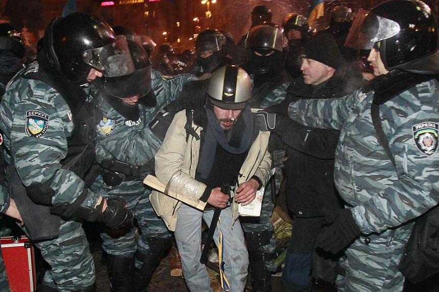 Riot police officers detaining a protester in Kiev on Wednesday, December 11, 2013. Ukrainian riot police moved in force early on Wednesday into part of the Kiev square where protesters are demonstrating against a government decision to rebuild trade