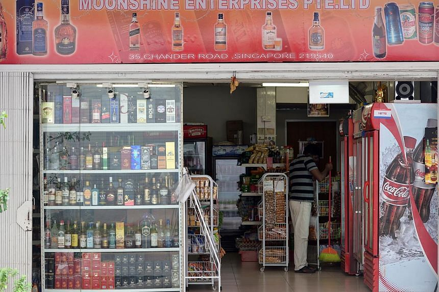 An employer at a liquor store in Little India cleans the shop before the day begins on Dec 10, 2013. Liquor store owners in Little India will not be allowed to sell any alcohol from Saturday until Monday morning, as the temporary ban on the sale and