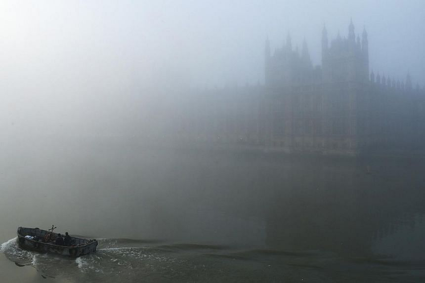 A boat on the River Thames passes the Houses of Parliament, in heavy fog in central London, on Wednesday, Dec 11, 2013. -- PHOTO: REUTERS
