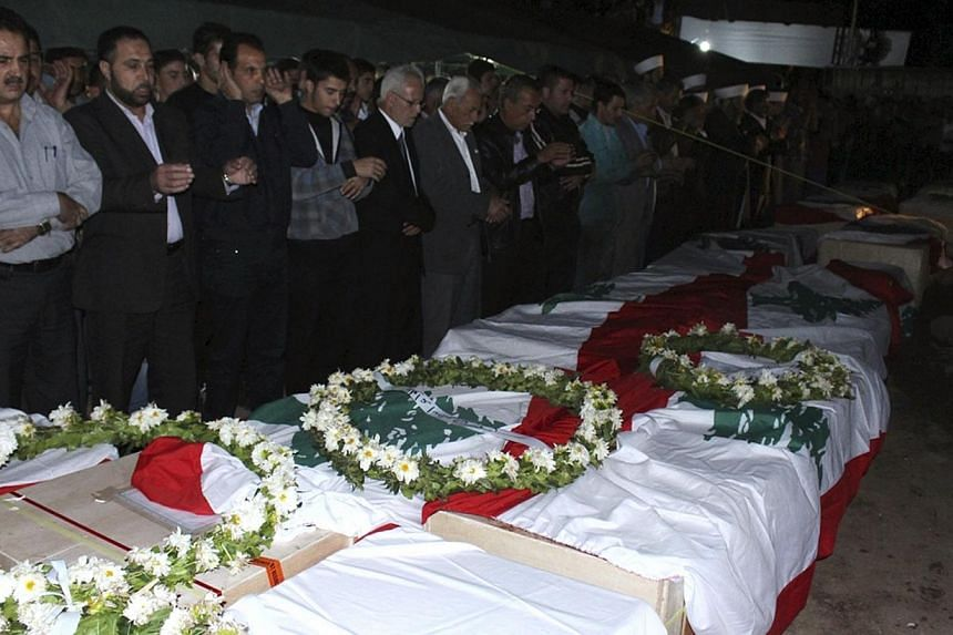 Religious personnel and relatives of the people who died when a boat carrying migrants sank off Indonesia last month, attend their funeral in Akkar Oct 31, 2013. Rights group Amnesty International has urged Australia to review its asylum seeker polic