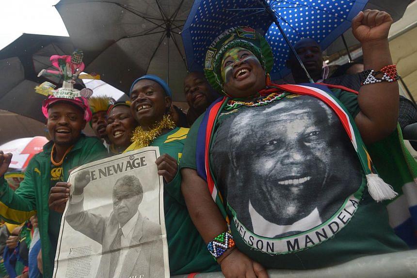 People celebrating the life of freedom icon Nelson Mandela during the memorial service for the former South African president at the Soccer City Stadium in Johannesburg on Tuesday, Dec 10, 2013. South Africans will form a guard of honour on Wednesday