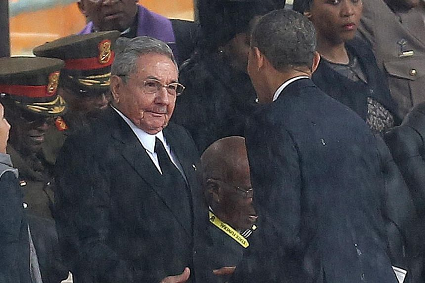 United States President Barack Obama shakes hands with Cuban President Raul Castro at the FNB Stadium in Soweto, South Africa, in the rain for a memorial service for former South African President Nelson Mandela, on Dec 10, 2013.Republicans wer