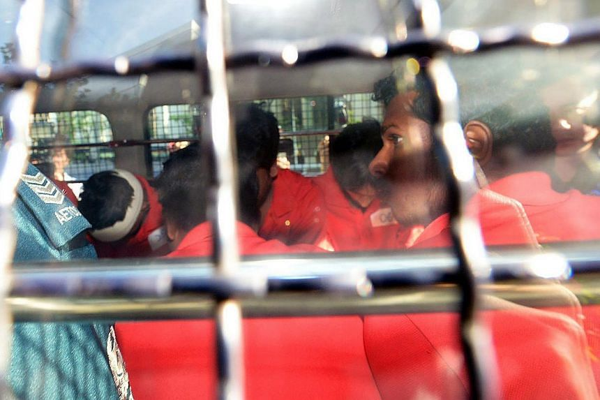 Arrested riot suspects arriving at the courts yesterday. The Indian nationals holding work permits did not bear visible injuries, except for one, whose head was bandaged. -- ST PHOTO: JAMIE KOH