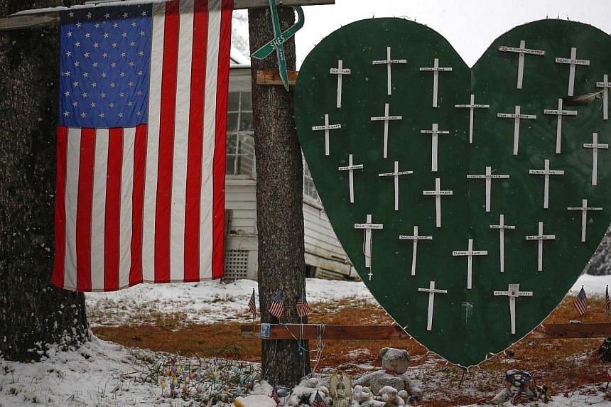 A memorial outside a home in Sandy Hook, Connecticut,on Dec 10, 2013,honouring the victims killed in the Sandy Hook Elementary School shooting.US President Barack Obama this weekend will mark the one year anniversary of the Sandy Ho