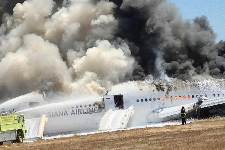 An Asiana Airlines Boeing 777 plane is engulfed in smoke on the tarmac after a crash landing at San Francisco International Airport in California on July 6, 2013, in this handout file photo provided by passenger Eugene Anthony Rah, released to Reuter