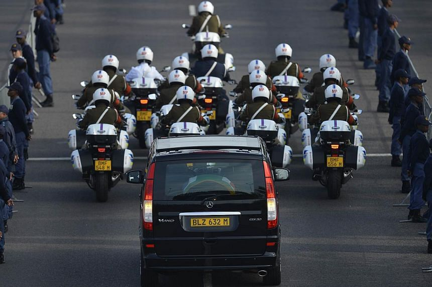 The funeral cortege of South Africa's former President Nelson Mandela leaves the Military Hospital in Pretoria on Dec 11, 2013, marking the start of a three-day lying in state. -- PHOTO: AFP