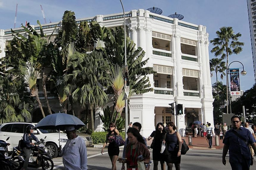 Pedestrians cross a traffic junction at the Raffles Hotel Shopping Arcade, on Nov 29, 2013. Manpower was the hottest topic for contributors to government feedback unit Reach this year, accounting for about a tenth of the more than 43,000 pieces