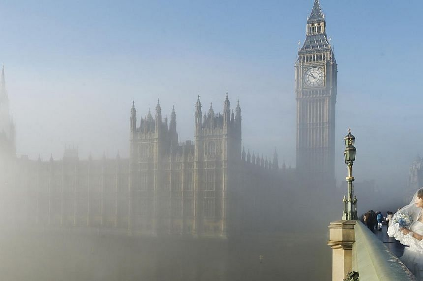 A bride poses for a photograph on Westminster Bridge as the fog clears in central London,on Wednesday, Dec 11, 2013. -- PHOTO: REUTERS