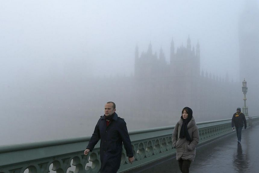 Pedestrians cross Westminster Bridge on a foggy day in central London,on Wednesday, Dec 11, 2013. -- PHOTO: REUTERS