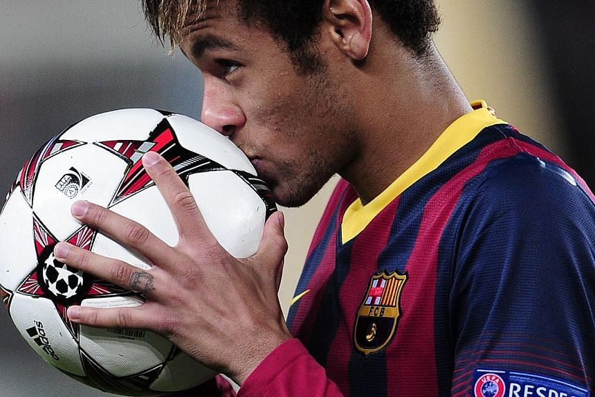 Barcelona's Brazilian forward Neymar with the match ball after scoring a hat-trick in the Champions League Group H football match between Barcelona and Celtic at the Camp Nou stadium in Barcelona on Wednesday, December 11, 2013. Barcelona coach