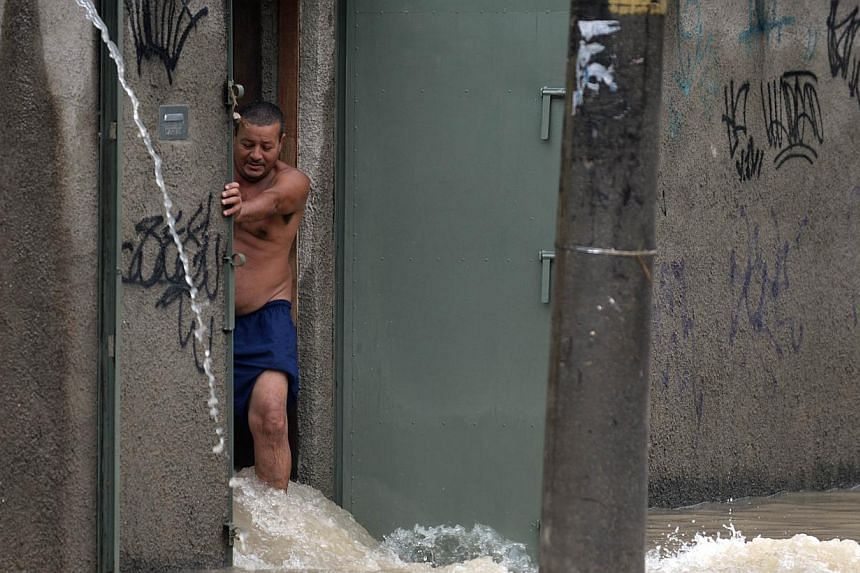 A man opening the entrance of his home to drain water out into a flooded street of a suburb in Rio de Janeiro on Wednesday, December 11, 2013. Alert was declared in Rio due to torrential rains falling since early morning. Fire officials reported one