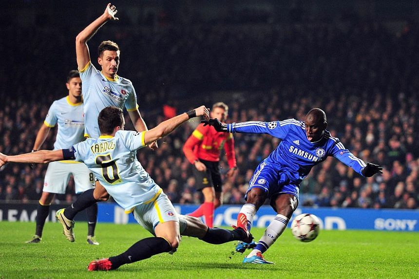 Chelsea's Senegalese striker Demba Ba (in blue) shooting past Steaua Bucharest's Romanian defender Florin Gardos (left) during the Champions League Group E match between Chelsea and Steaua Bucharest at Stamford Bridge on Wednesday, December 11, 2013.