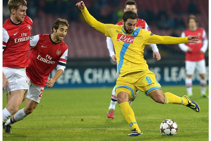 Napoli's Argentinian forward Gonzalo Higuain (centre) kicks to score during the Uefa Champion's League group F football match between SSC Napoli and Arsenal FC at the San Paolo Stadium in Naples on Dec 11, 2013. Napoli were robbed of a place in the C