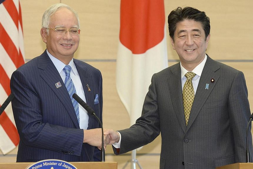 Japan's Prime Minister Shinzo Abe (R) shakes hands with his Malaysian counterpart Najib Razak (L) at the end of a media announcement after their talks at Abe's official residence in Tokyo Dec 12, 2013. -- PHOTO: REUTERS