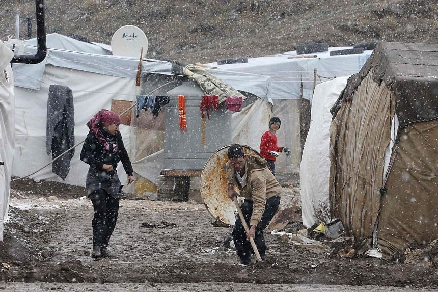 A Syrian refugee works outside his tent during a winter storm in Zahle town, in the Bekaa Valley Dec 11, 2013. -- PHOTO: REUTERS