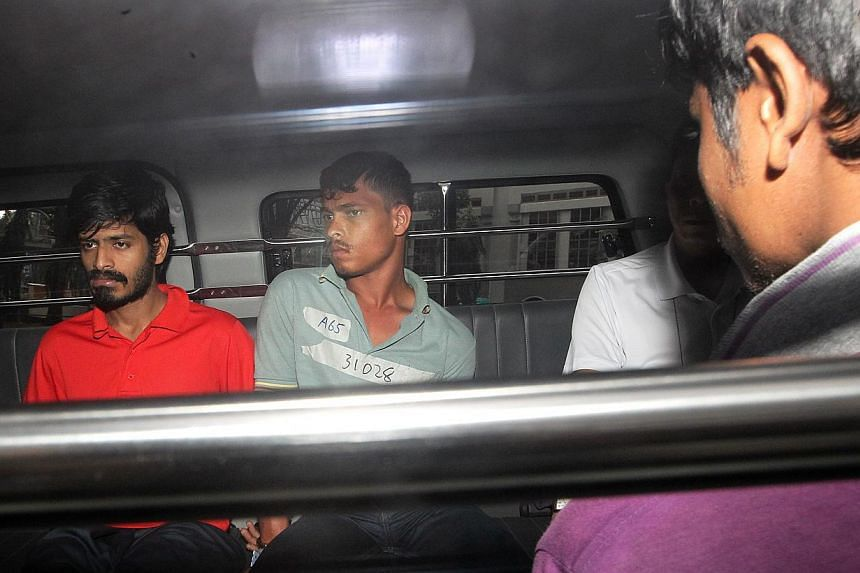 The three Indian nationals who were charged with rioting yesterday being taken to court. They were alleged to have smashed the windscreen and window of the private bus that had run over the man who died. -- ST PHOTO: LAU FOOK KONG