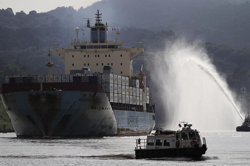 A tug boat sprays water on a cargo ship to celebrate the upcoming 100th anniversary of the start of operations in the Panama Canal, which will be marked in 2014, as it travels towards the Culebra cut in Gamboa near Panama City on Wednesday, Dec 11, 2