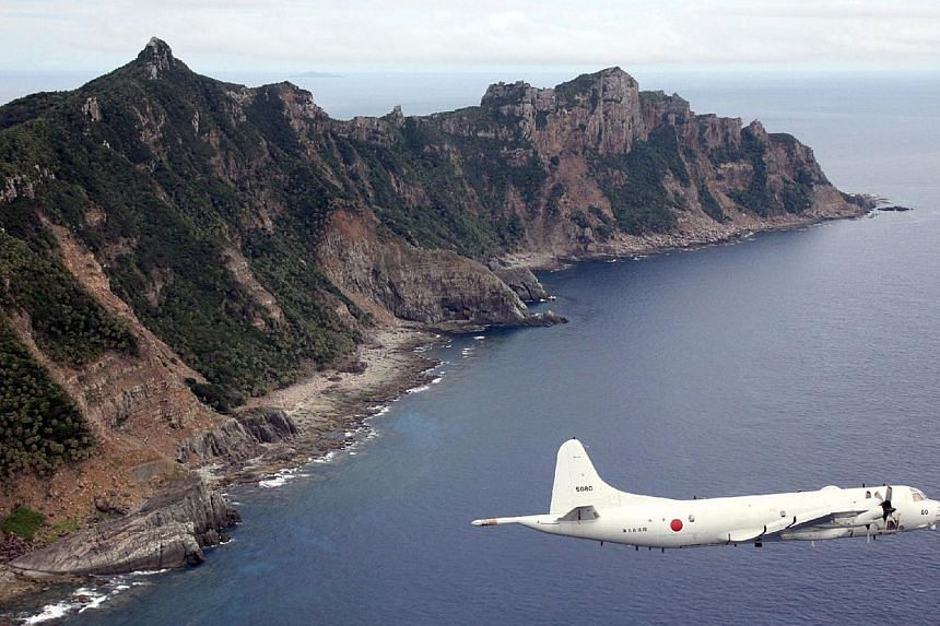 This photo taken on Oct 13, 2011, shows a P-3C patrol plane of Japanese Maritime Self-Defence Force flying over the disputed islets known as the Senkaku islands in Japan and Diaoyu islands in China, in the East China Sea. The navies of Japan and