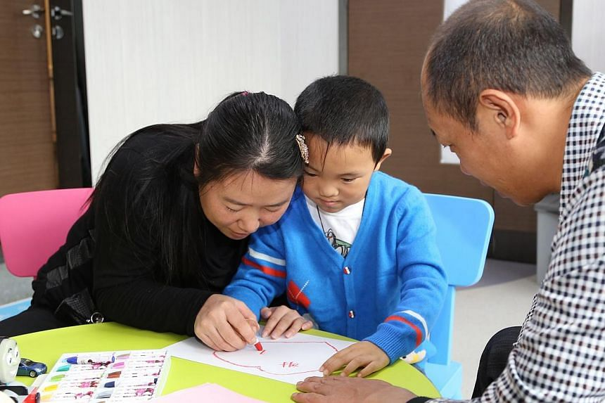 This handhout picture released and taken by the C-MER Dennis Lam Eye Hospital on Wednesday, Dec 11, 2013, shows six-year-old Guo Bin - known as Bin Bin - (centre), who had his eyes gouged out in August, writing with the help of his mother and father,