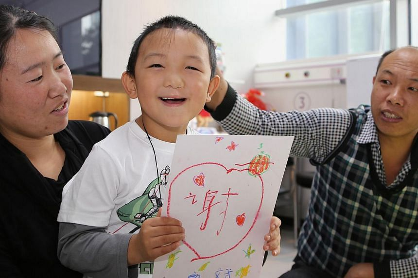This handhout picture released and taken by the C-MER Dennis Lam Eye Hospital on Wednesday, Dec 11, 2013, shows six-year-old Guo Bin - known as Bin Bin - (centre), who had his eyes gouged out in August, smiling next to his mother and father while hol