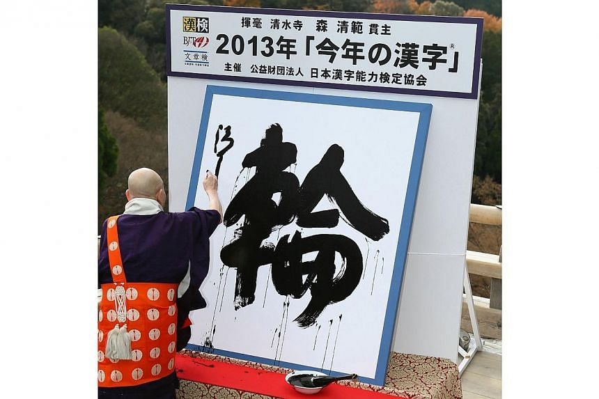 Seihan Mori, the chief priest of Kyoto's famous Kiyomizu temple, displays his caligraphy of a kanji (or Chinese character), wa meaning ring, which was selected as the single best kanji to symbolize the year 2013 at the temple in Kyoto, western Japan