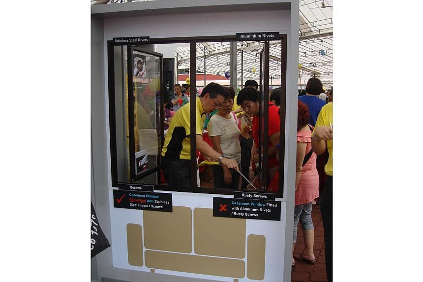 A Building and Construction Authority officer (in yellow shirt) providing residents with window safety tips at a roving exhibition in Bukit Batok in May 2012. The number of fallen windows this year is the lowest in five years, said the Authority on T