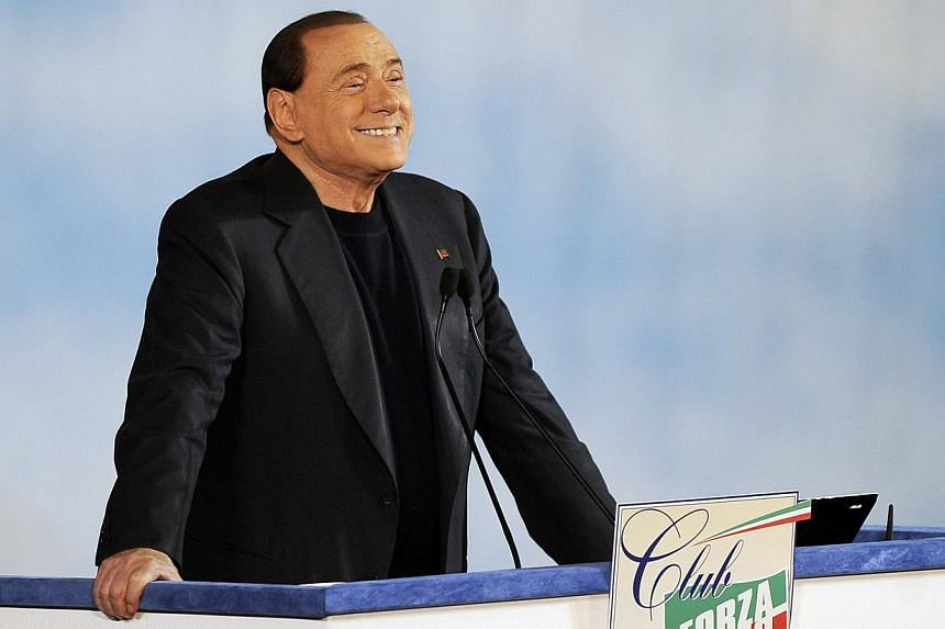 """Former Italian prime minister Silvio Berlusconi reacts as he attends a rally to launch the """"Forza Silvio"""" club in downtown Rome on Dec 8, 2013. Scandal-tainted Berlusconi, sentenced to a year in prison for tax fraud, claimed on Thursday there would b"""