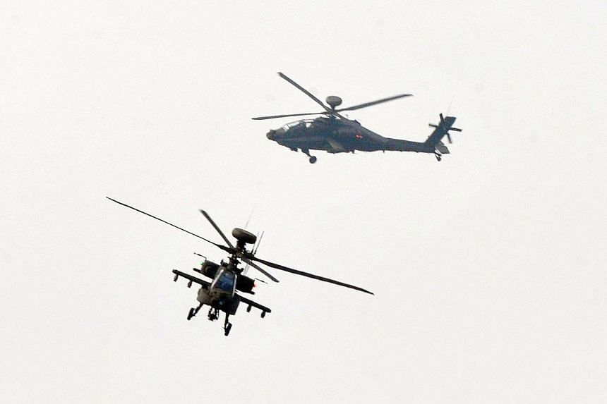Two AH-64E Apache attack helicopters fly during a ceremony in an army airbone special force unit in Tainan, southern Taiwan on Dec 13, 2013. Taiwan displayed its new fleet of US-made Apache attack helicopters on Friday. -- PHOTO: AFP