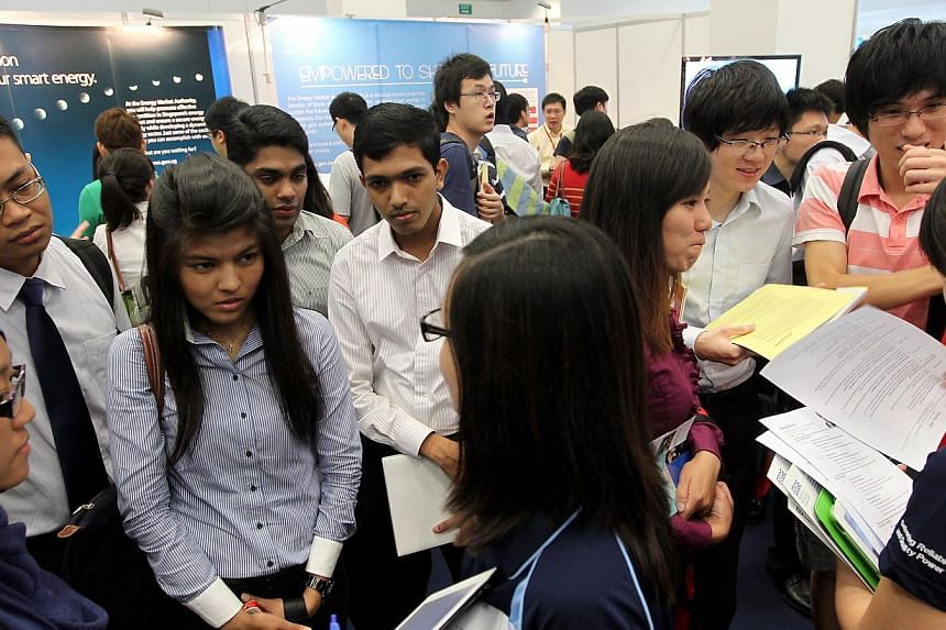 Job seekers at the Nanyang Technological University's (NTU) Career Fair 2013 listening to recruiters at a new pavilion featuring jobs in the energy sector. Amid low unemployment and continued strong job growth, there were fewer job seekers and more