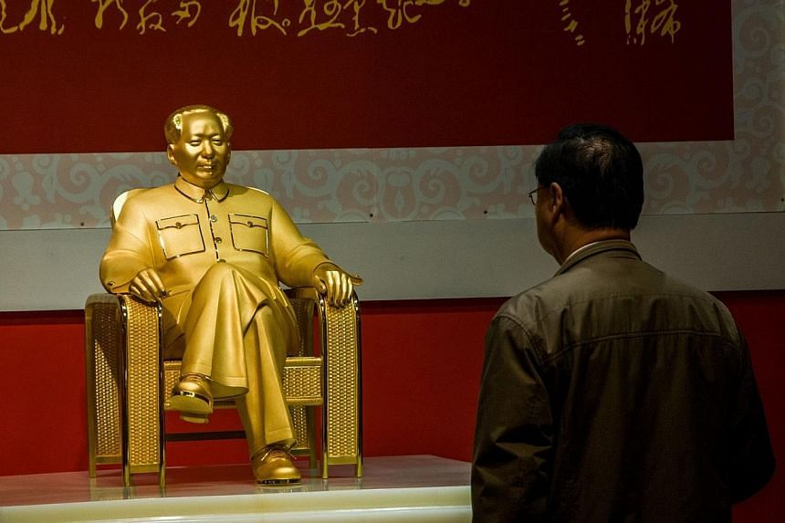 A man looks at a gold and jade statue of Mao Zedong displayed at an exhibition in Shenzhen, south China's Guangdong province on Dec 13, 2013. -- PHOTO: AFP