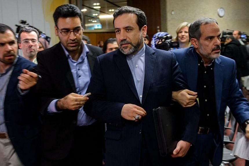 Iran's Deputy Foreign Minister Abbas Araqchi (C) is surrounded by journalists following a press conference closing the third day of talks on Iran's nuclear programme, on Nov 10, 2013 in Geneva. -- PHOTO: AFP