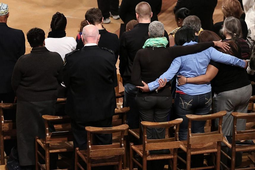 Family members of shooting victims pray on stage during the National Vigil for Victims of Gun Violence at the Washington National Cathedral in Washington, DC, on Dec 12, 2013. The event was to mark the first anniversary of the Dec 14, 2012 shooting t