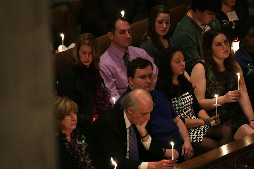 Friends and families of Sandy Hook shooting hold candles during the National Vigil for Victims of Gun Violence on Dec 12, 2013, at the Washington National Cathedral in Washington, DC. The event was to mark the first anniversary of the Dec 14, 2012 sh