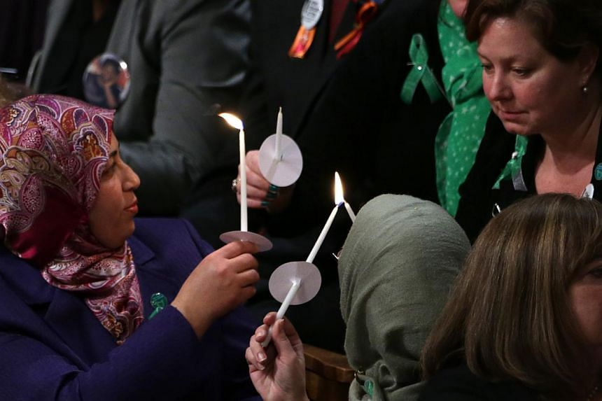 Families of shooting victims light candles on stage during the National Vigil for Victims of Gun Violence on Dec 12, 2013 at the Washington National Cathedral in Washington, DC. The event was to mark the the first anniversary of the Dec 14, 2012 shoo