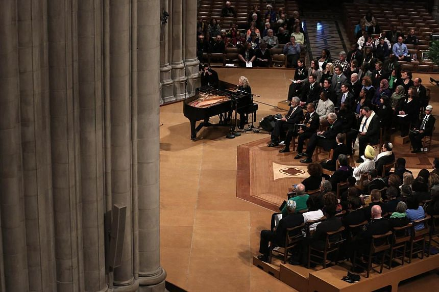 Singer-songwriter Carole King (centre) performs during the National Vigil for Victims of Gun Violence on Dec 12, 2013 at the Washington National Cathedral in Washington, DC. The event was to mark the first anniversary of the Dec 14, 2012 shooting tha