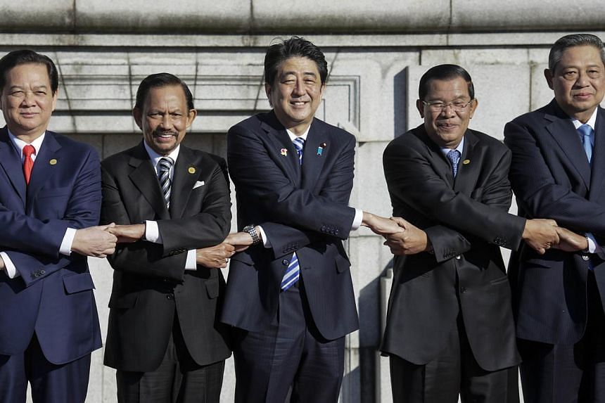 Asean leaders hold hands for a photo session of Japan-Asean Commemorative Summit at Akasaka State Guesthouse in Tokyo on Dec 13, 2013. (From left) Vietnam's Prime Minister Nguyen Tan Dung, Brunei King Hassanal Bolkiah, Japan's Prime Minister Shinzo A