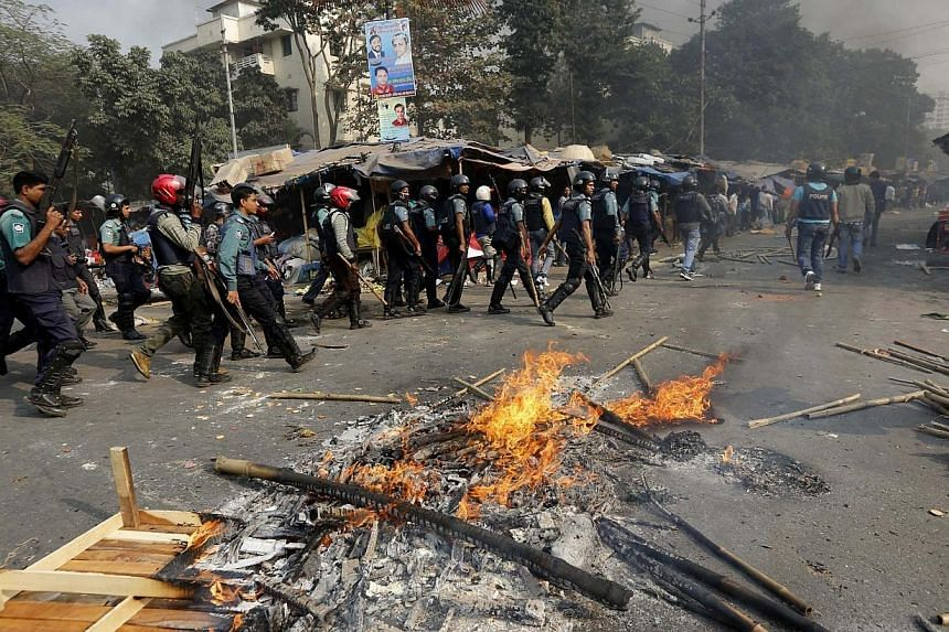 Police officers conduct a raid in an area after clashes with Bangladesh's Jamaat-e-Islami party activists in Dhaka, on Dec 13, 2013. Six people were killed in Bangladesh including three protesters who were shot dead by police on Saturday, Dec 14, 201