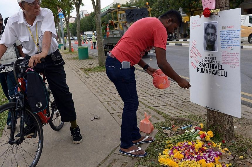 Freelance artist Suresh Vanaz leaving flowers in front of a tribute board set up in memory of accident victim Sakthivel Kumaravelu at the junction of Race Course Road and Tekka Lane. An Ophir Road Catholic church will hold a memorial Mass on Sunday f
