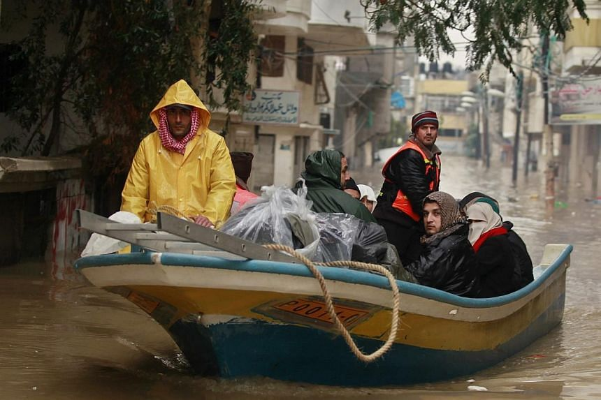 Members of Palestinian civil defense operate a boat as they evacuate people after their houses were flooded with rainwater on a stormy day in the northern Gaza Strip, on Dec 14, 2013. More than 4,000 people have been evacuated from flood-damaged home