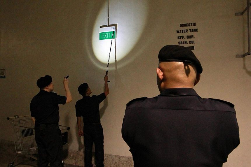 Officers from the Singapore Civil Defence Force (SCDF) find a faulty exit light at the basement carpark of VivoCity during an enforcement blitz on fire safety.-- ST PHOTO:NEO XIAOBIN
