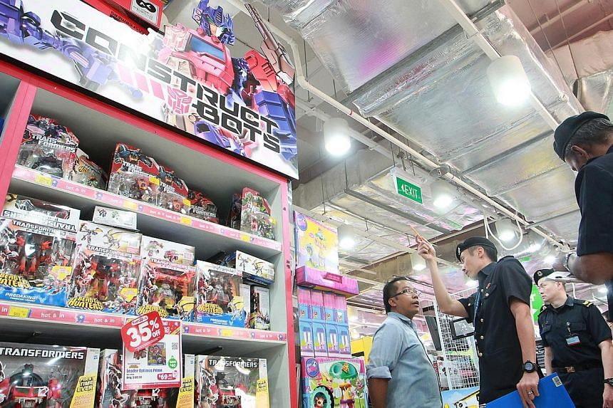 """Captain Neo Jin Xiang (second from left), 30, enforcement team leader from the Central Enforcement Department, speaks to a staff from Toys """"R"""" Us at VivoCity about the shelf display objects being stacked too high which affects the path of the fire sp"""