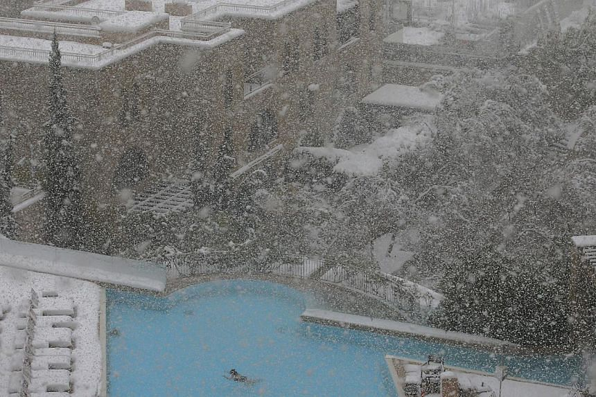 A woman swims in the pool at the David Citadel Hotel during a snowstorm in Jerusalem, on Friday, Dec 13, 2013. Israel was on Saturday, Dec 14, 2013, lashed by a fierce winter storm, with access to cities and towns on high ground cut off by anoth