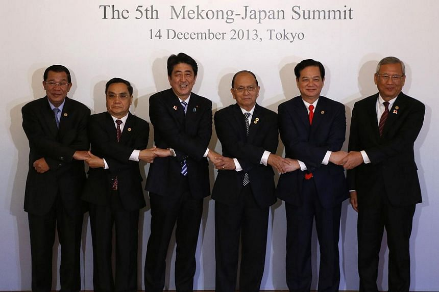 Japan's Prime Minister Shinzo Abe (third from left) poses for a photo with(from left) Cambodia's Prime Minister Hun Sen, Laos' Prime Minister Thongsing Thammavong, Myanmar's President Thein Sein, Vietnam's Prime Minister Nguyen Tan Dung and Tha