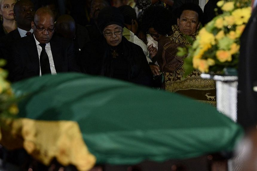 South African President Jacob Zuma (left), and Mandela's ex-wife Winnie Mandela Madikizela attend a farewell service for former South African president Nelson Mandela, on Saturday, Dec 14, 2013, at the Waterkloof air force base in Pretoria. South Afr