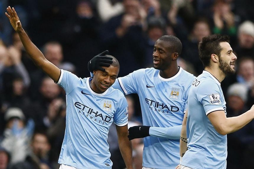 Manchester City's Fernandinho (left) celebrates with teammates after scoring against Arsenal in their English Premier League match at the Etihad Stadium in Manchester, on Saturday, Dec 14, 2013. City exposed the first cracks in Arsenal's title challe